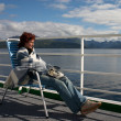 Girl sitting on the cruise liner deck — Stockfoto