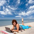 Woman with laptop at sea beach — Stock Photo #1590330