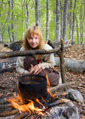 Girl sitting near of bonfire in forest — Stockfoto