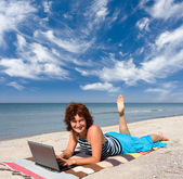 Woman with laptop at sea beach — Stock Photo