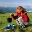 Hiker girl making a coffee - Stock Photo