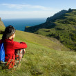 Woman sitting on a hill over sea - Stock Photo