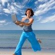 Smiling girl running with laptop — Stock Photo #1807887