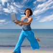 Smiling girl running with laptop - Stock Photo