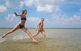 Girls running and jumping above water — Stock Photo