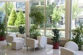 Luxury interior with big window and white armcha — Stock Photo