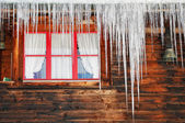 Icicles on wooden house — Stock Photo