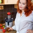 Redhaired woman makes apple juice — Stock Photo