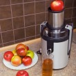 Juicer, apples, a glass of juice - Stock Photo