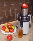 Juicer, apples, a glass of juice — Stock Photo