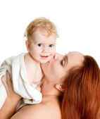 Mother kissing baby girl in a towel afte — Stock Photo