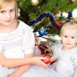 Girl gives christmas ball her sister — Stock fotografie