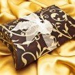 Gift at golden fabric — Stock Photo