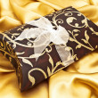 Stock Photo: Gift at golden fabric