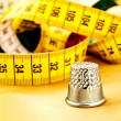 Measuring tape and thimble - Stock Photo