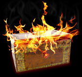 Old rusty metal chest with flame tails escaping out of cover against the black background — Stock Photo