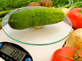 Cucumber on the scales — Stock Photo