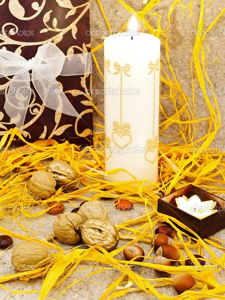 Holiday decoration with gift box, candles and nuts against beige background — Stock Photo #1498643