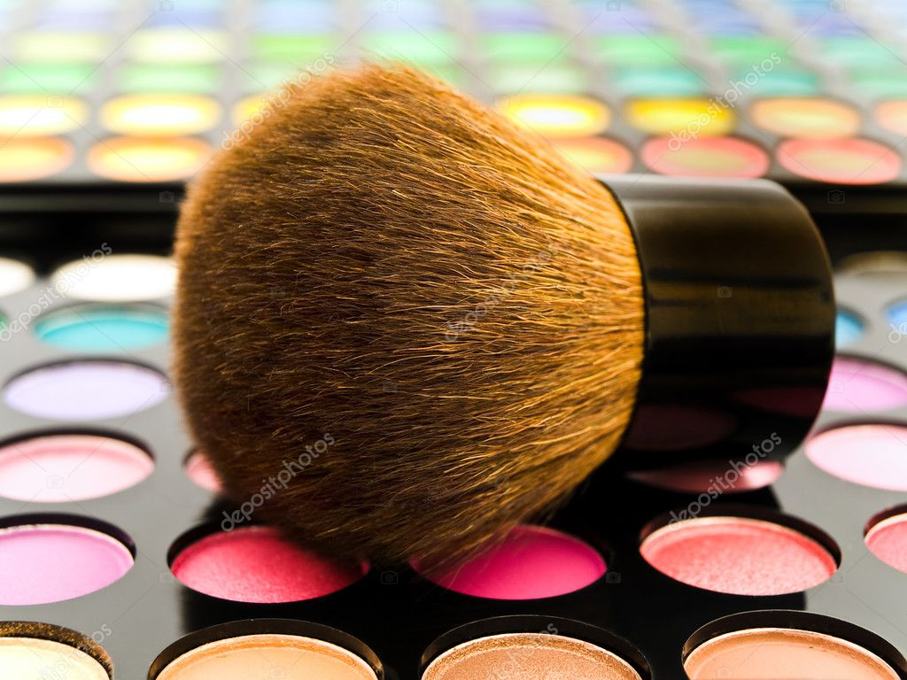 Cosmetics brush over multicolored eye shadows against the white background — Stock Photo #1499975