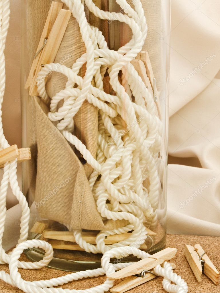 Composition with clothespins, cord and vase against beige textile background — Stock Photo #2288483