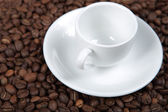 The white coffee cup on coffee beans — Stock Photo
