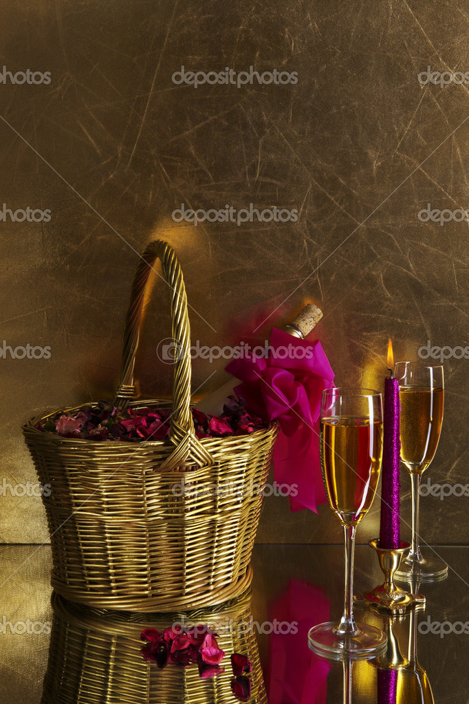 Two glasses of champagne, a candle and a bottle of wine in a golden basket with rose petals on a gold background — Photo #1666104