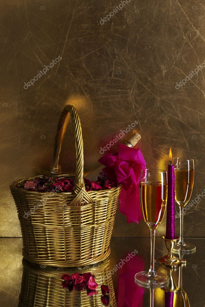 Two glasses of champagne, a candle and a bottle of wine in a golden basket with rose petals on a gold background   #1666104