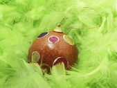 Green feathers and Christmass ball — Stock Photo