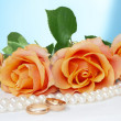 Necklace, roses and wedding rings - Stock Photo