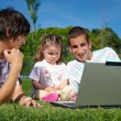 Two guys and a little girl with a laptop — Stock Photo