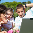 Two guys and little girl with laptop — Stock Photo #1502054