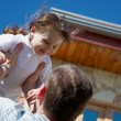 Father tossing up his daughter — Stock Photo