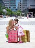 亲吻她的母亲在一圈的 shoppingbags 街的女儿 — 图库照片