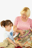 Grandmother and granddaughter embroider — Stock Photo