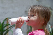 Little girl drinking yogurt — Stock Photo