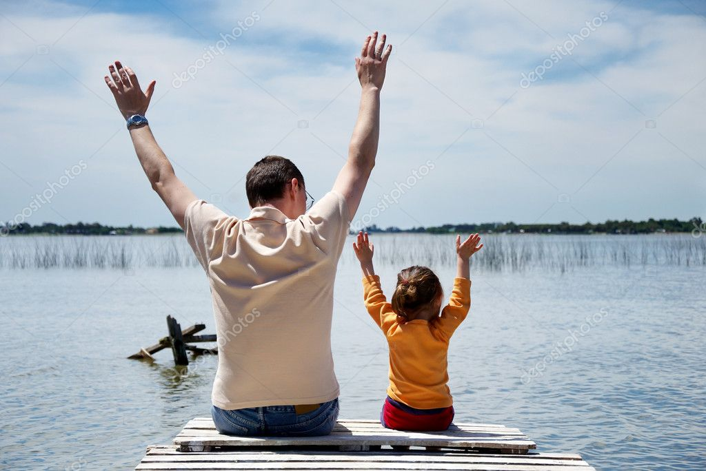 Father and daughter sitting on pier at the lake — Stock Photo #1508289