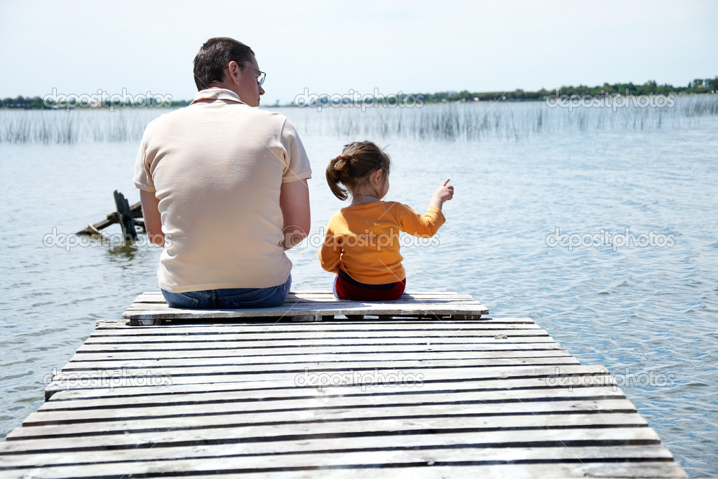 Father and daughter sitting on pier at the lake — Photo #1508313