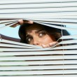 Girl looking through the blinds — Stock Photo