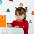 Little girl plays a colorful cubes — Stock Photo #1515527