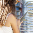 Girl looks through blinds — Stock Photo