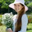 Girl in the hat with flowers — Stock Photo