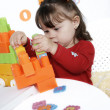 Little girl plays a colorful cubes — Stockfoto
