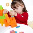 Little girl plays a colorful cubes — Stock Photo #1515652