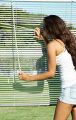 Girl looks through blinds — Stock Photo