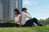 Man and woman sitting in a park — Stock Photo