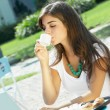 Beautiful girl eating in a cafe on the street — Stock Photo #1530797