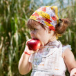 Little girl eats peach - Stock Photo