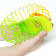 Spring toy in the hands of a child - Stock Photo