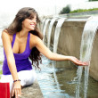 Beautiful girl sits at the water fountain — Stock Photo