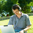 Guy listens music on a laptop — Stock Photo